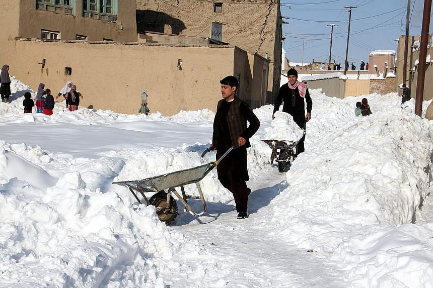 People removing snow from their home compounds in Ghazni, Afghanistan, on Sunday. A series of avalanches over the weekend destroyed dozens of homes and killed livestock, mostly in central and northern provinces. The death toll across the country reac