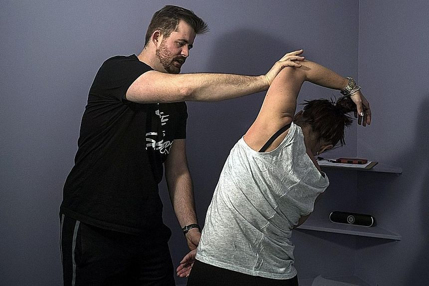 A stretch coach at Power Stretch Studios in Manhattan cupping her hand over the tight muscles on a client's shoulder blade, to compress it and help it stretch and release. Coaches help clients loosen overworked and contracted muscles (above) and also