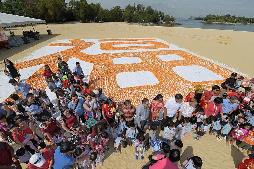 More than 500 children and their parents turned up at Palawan Beach in Sentosa yesterday to create a record-breaking feat using 12,888 mandarin oranges. Measuring 20m by 20m, it entered the Singapore Book Of Records as the largest Chinese character ""