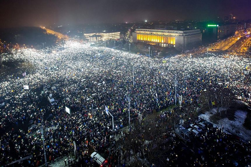 Protesters lighting up the Victoriei Plaza, outside the Romanian government headquarters in Bucharest, on Sunday, demanding the Cabinet resign.