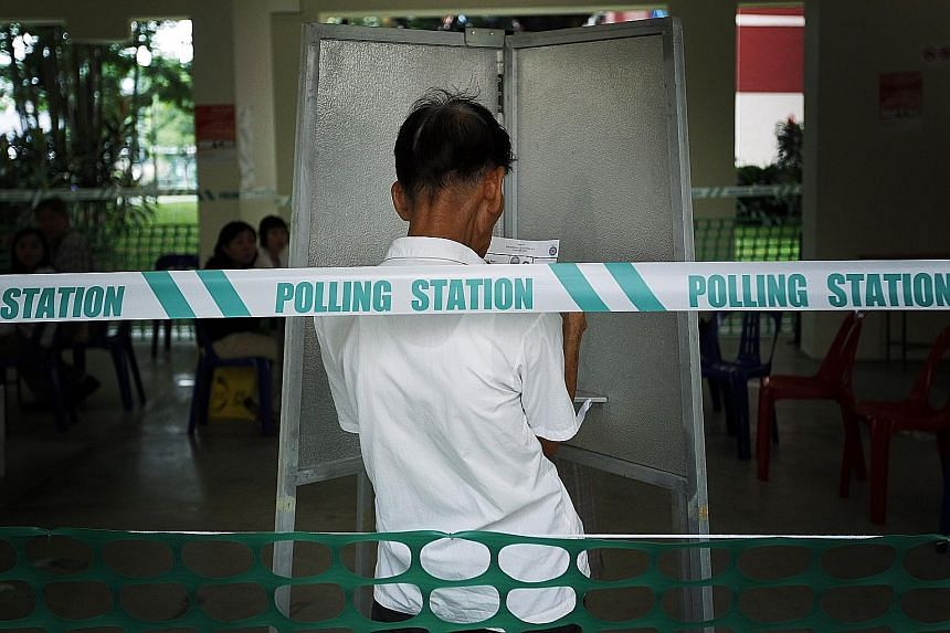 A voter in a Toa Payoh Lorong 2 polling station studying his ballot slip in the last presidential election in 2011. The presidential election this year will be held in September, so that the campaign period will not coincide with National Day celebra