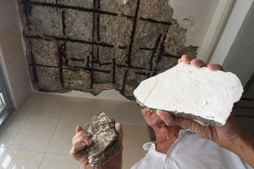 Mr Li Zhanwu holding up pieces of the ceiling which fell.