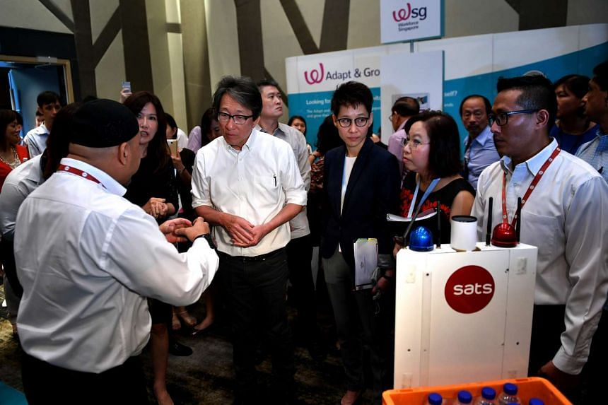 An autonomous guided vehicle from Sats being shown to Manpower Minister Lim Swee Say during the career fair on Feb 8, 2017.