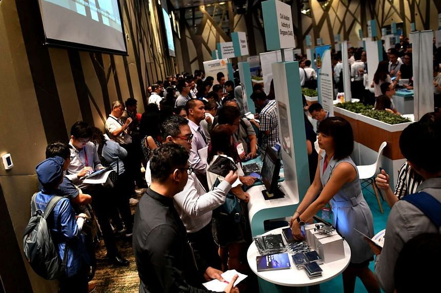 People look at brochures and booths during the career fair at Crowne Plaza Changi Airport on Feb 8, 2017.
