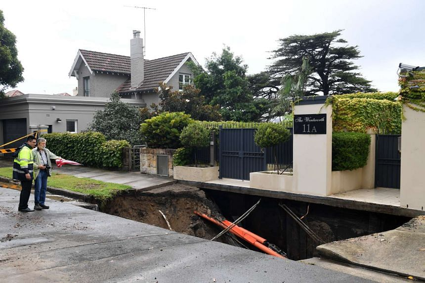 A man looks into a sinkhole which has opened up in the suburb of Point Piper in Sydney on Feb 8, 2017.