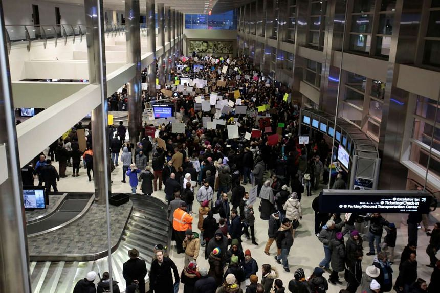 Protestors fill the baggage claim area during a rally against a temporary travel ban signed by US President Donald Trump at Detroit Metropolitan airport in Romulus, Michigan on Jan 29, 2017.
