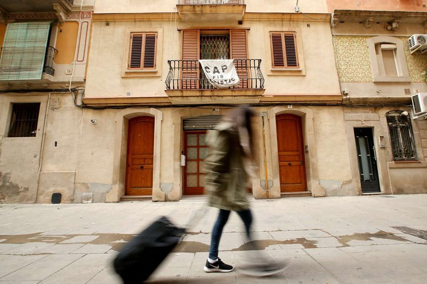 A banner against apartments for tourists hangs from a balcony as a woman pulls a suitcase at Barceloneta neighborhood in Barcelona, Spain, on Nov 28, 2016.