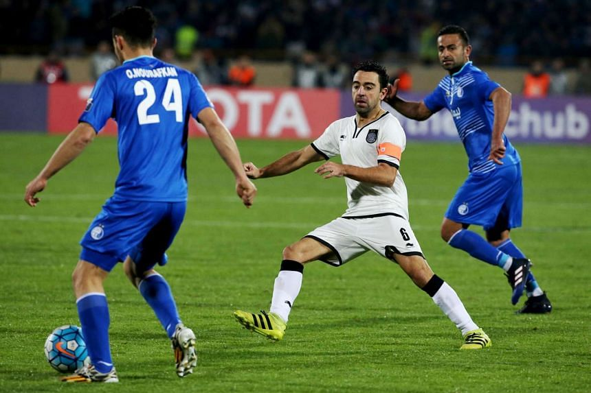 Qatar's Al-Sadd player Xavi fighting for the ball against Omid Nor Afkan (left) and Omid Ebrahimi (right) of Iran's Esteghlal during their AFC Champions League playoff football match at the Azadi stadium in Tehran, on Feb 7, 2017.