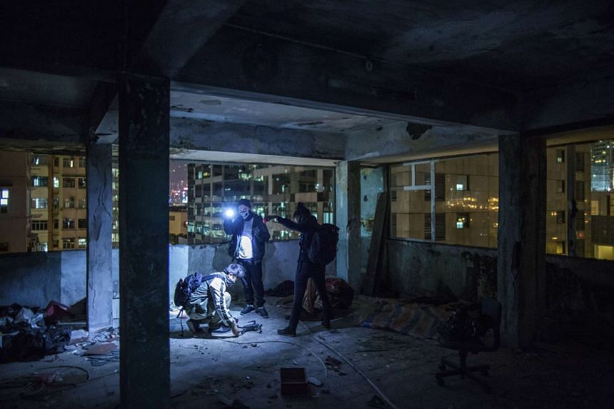 Members of HK Urbex prepare to use a drone to film video in an abandoned building in Hong Kong's Tai Kok Tsui district.