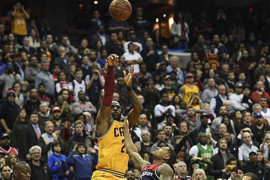 LeBron James of the Cleveland Cavaliers shooting a dramatic three-pointer over the Washington Wizards' Bradley Beal to tie the score at 120-120 and force the game into overtime on Monday. The Cavaliers went on to wrap up a 140-135 victory.
