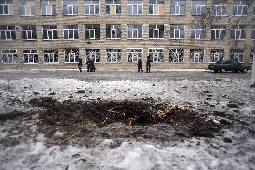 A shell hole is seen in front of a school in Avdiivka, Donetsk area, Ukraine, on Monday. Ukrainian forces and pro-Russian separatists have both blamed each other for the latest flare-up as the two-year-old Minsk peace deal has merely locked the two s