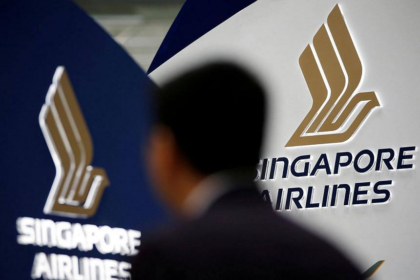 A man walks past a Singapore Airlines signage at Changi Airport in Singapore.