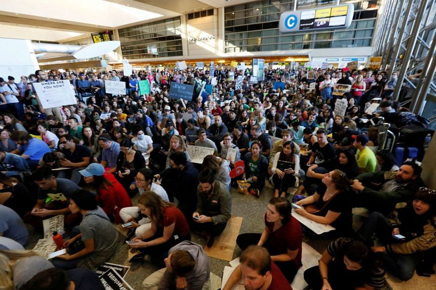 Demonstrators sit inside the LAX international terminal and yell slogans during protest against the travel ban imposed by US President Donald Trump's executive order on Jan 29, 2017.