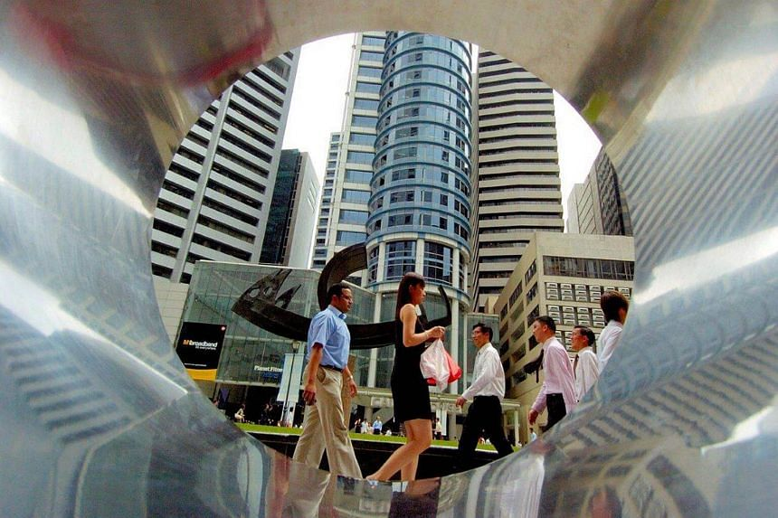 Business people walk through Raffles Place, Singapore's central business district.