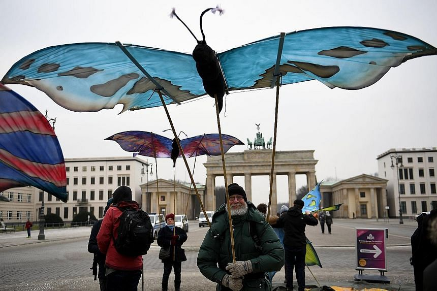 Environmentalists protesting against the use of glyphosate herbicides in agriculture, with giant butterfly mock-ups in front of a major Berlin landmark, the Brandenburg Gate, yesterday. Glyphosate is suspected of being carcinogenic in humans.