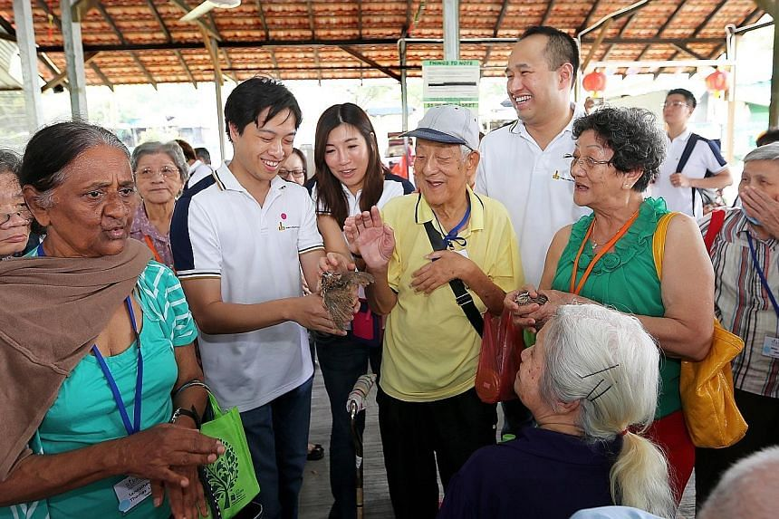 Hong Leong Foundation governor Kwek Eik Sheng showing a quail to seniors from the Henderson Senior Citizens' Home and St John's Home for Elderly Persons at the Farmart Centre in Sungei Tengah Road. Sixty elderly beneficiaries from the two facilities