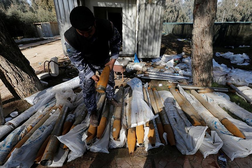 An Iraqi federal police officer inspecting weapons used by ISIS militants in Mosul.