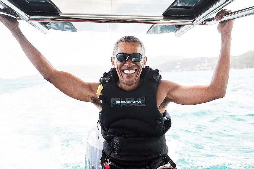 Left: Mr Obama relaxing with Mr Branson on a boat off the coast of Moskito Island, which is owned by the Virgin Group founder. Below: Mr Obama spent two days learning kitesurfing, in which people ride a board while being pulled behind a kite, Mr Bran