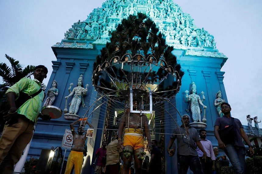 Devotees leave a temple in their kavadis during the Hindu festival of Thaipusam in Singapore on Feb 9, 2017.