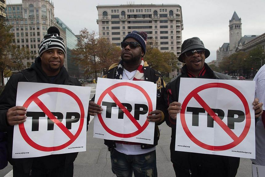 Men holding signs as they demonstrate against the Trans-Pacific Partnership (TPP) trade agreement in Washington, DC on Nov 14, 2016.
