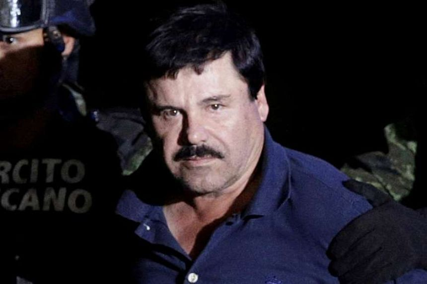 Drug lord Joaquin El Chapo Guzman is escorted by soldiers at the hangar belonging to the office of the Attorney General in Mexico City.