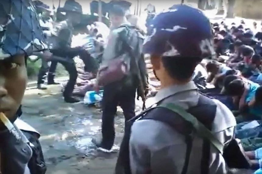 Screen grab from a YouTube video showing a policeman kicking a Rohingya minority villager seated on the ground in the village of Kotankauk during a police area clearance operation on Nov 5, 2016.