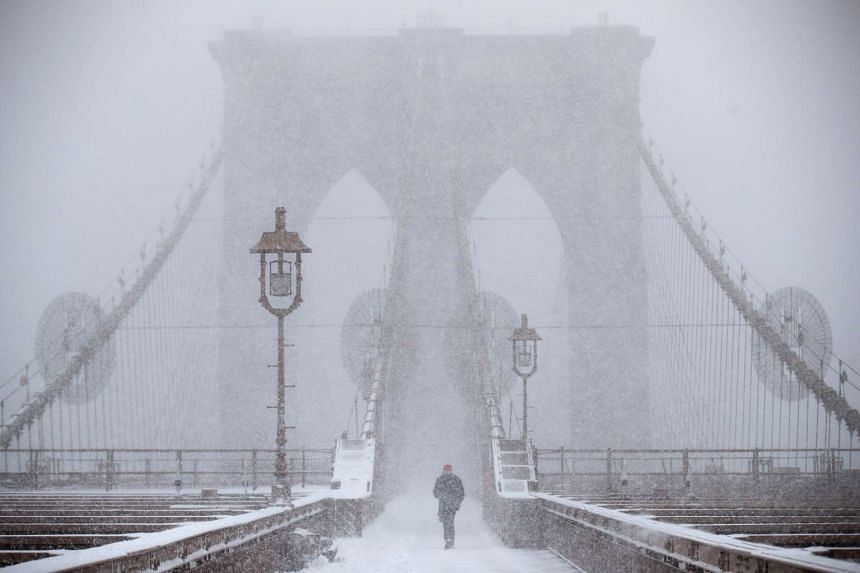 A man walks across the Brooklyn Bridge in the snow, on Feb 9, 2017 in New York City.