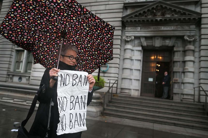 """A woman holds up a """"NO BAN"""" sign outside a federal appeals court on Feb 9, 2017, in San Francisco, California."""