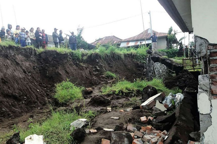 Villagers looking at a house which was damaged in a landslide in Kintamani, Bali province, on Feb 10, 2017.