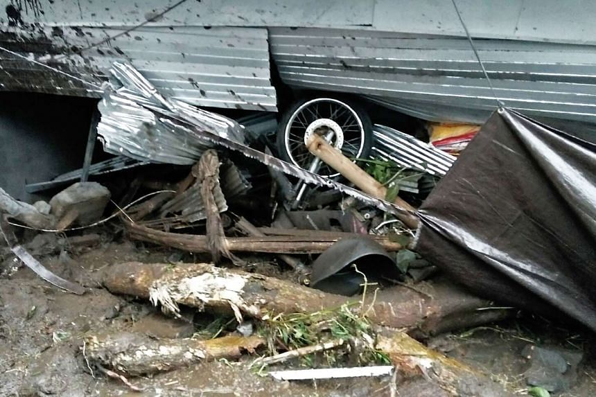 A motorcycle stuck under a house that was damaged in a landslide in Kintamani, Bali province, on Feb 10, 2017.