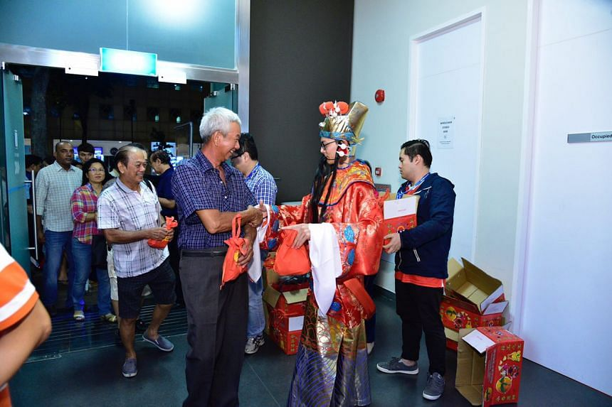 People shake hands with a man dressed as the God of Fortune mascot at the Singapore Pools building at 210 Middle Road, on Feb 10, 2017.