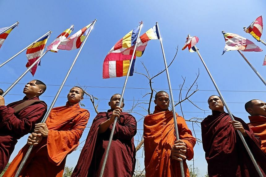 """Buddhist monks at Thilawa port in Yangon yesterday, to await the arrival of a ship carrying aid for the Rohingya. The monks want to send the message that there is """"no Rohingya"""" in the country."""