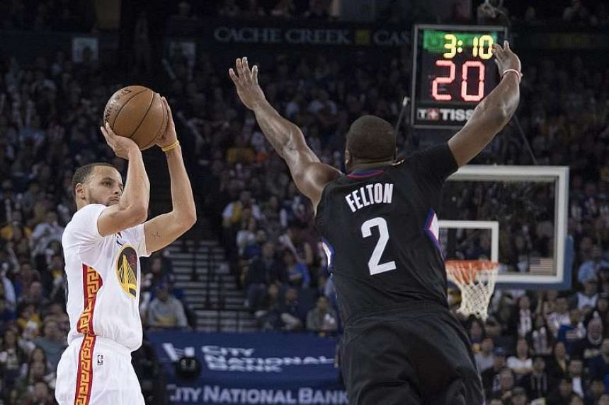 Golden State Warriors guard Stephen Curry (left) shooting against a lunging Raymond Felton of the Los Angeles Clippers on Saturday. Curry scored 43 points and Kevin Durant added 23 as the Warriors won 144-98.