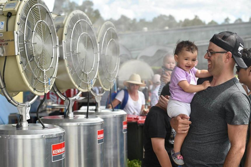 A father and his baby cool down in front of fans at the Sydney International tennis tournament.