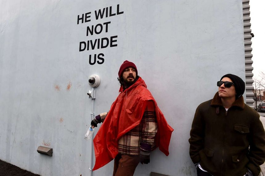 US actor Shia LaBeouf (left) is seen during his He Will Not Divide Us livestream outside the Museum of the Moving Image on Jan 24, 2017.