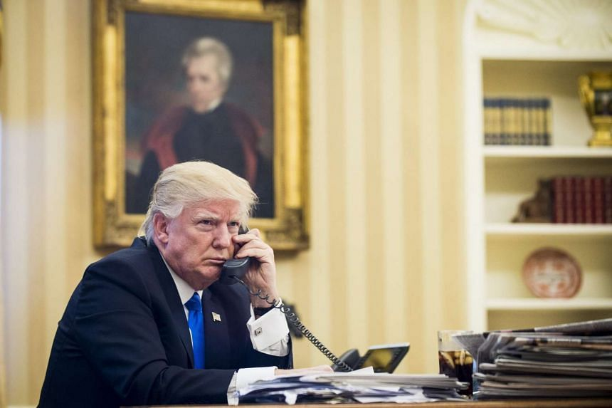 US President Donald Trump speaking on the phone with Prime Minister of Australia, Malcolm Turnbull, in the Oval Office in Washington, DC, on Jan 28, 2017.