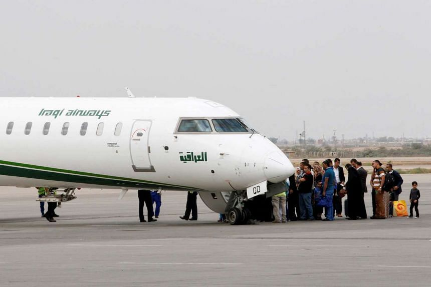 An Iraqi Airways plane and passengers at Baghdad International airport in a 2014 file photo.