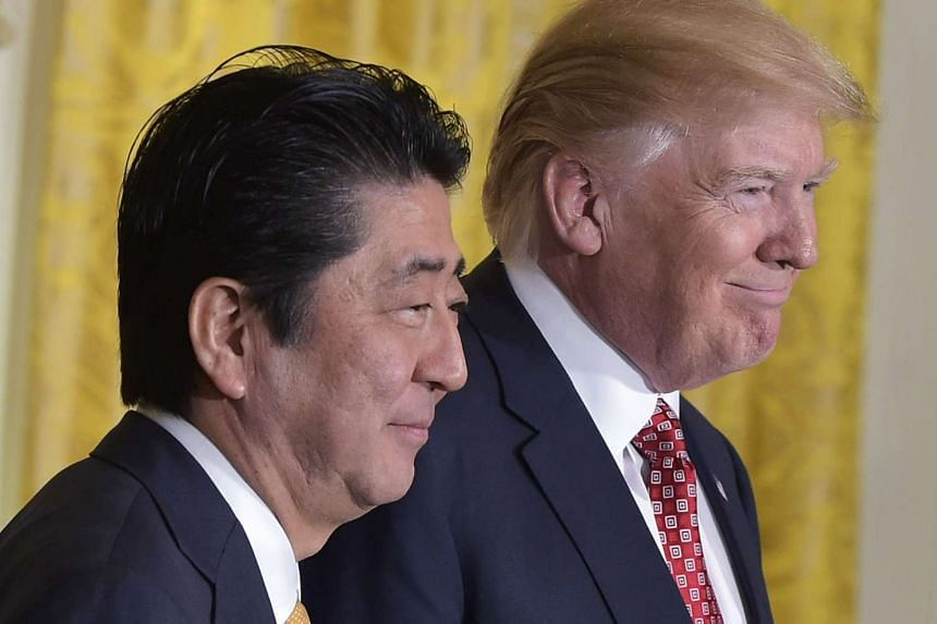 US President Donald Trump (right) and Japan's Prime Minister Shinzo Abe smile at the end of a joint press conference in the East Room of the White House in Washington, DC on Feb 10, 2017.