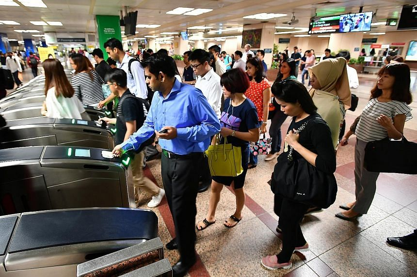 The morning crowd at Raffles Place around 9.15am yesterday. Passengers on the affected train had to alight there earlier.