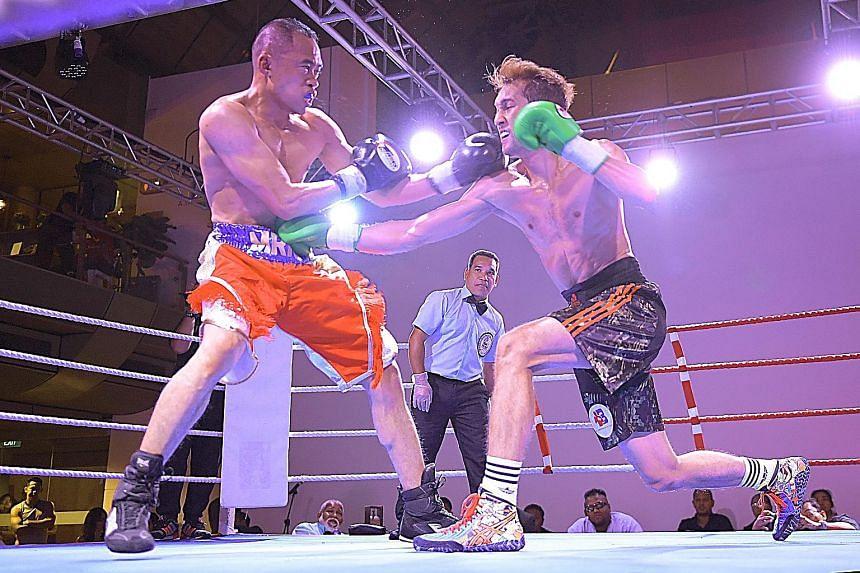 Singapore's Hamzah Farouk (black shorts) landing a right on Malaysian Rahmat Munadjab's midriff in their lightweight bout. He won by unanimous decision after a five-year break.