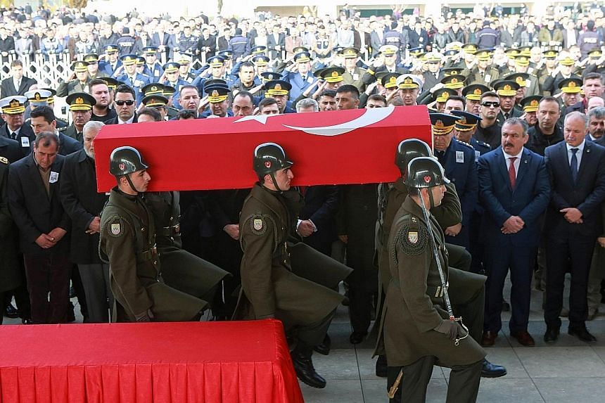 Military honour guards bearing the coffin of a Turkish soldier killed on Tuesday in an ISIS attack around Al-Bab in Syria. The funeral ceremony took place in Ankara in Turkey on Thursday, the same day that a Russian air strike in northern Syria inadv