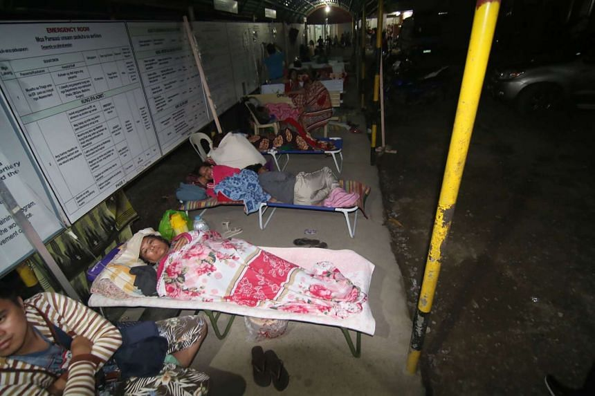 Hospital patients taking shelter in a pedestrian-waiting shed for safety after an earthquake in Surigao City, southern island of Mindanao, on Feb 11, 2017.