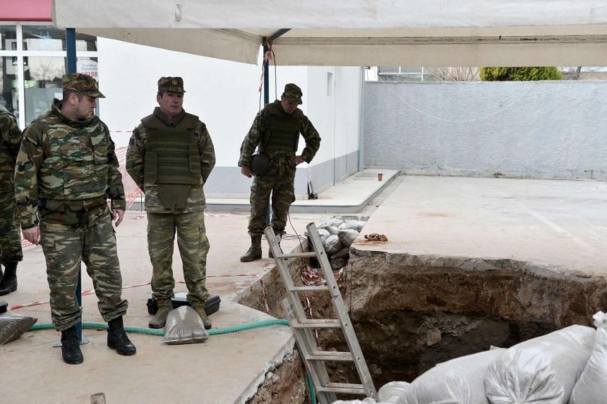 Members of the Greek Army's Explosive Ordnance Disposal team standing near the site of a WWII bomb that was found in Kordelio, a suburb of Thessaloniki, on Feb 12, 2017.