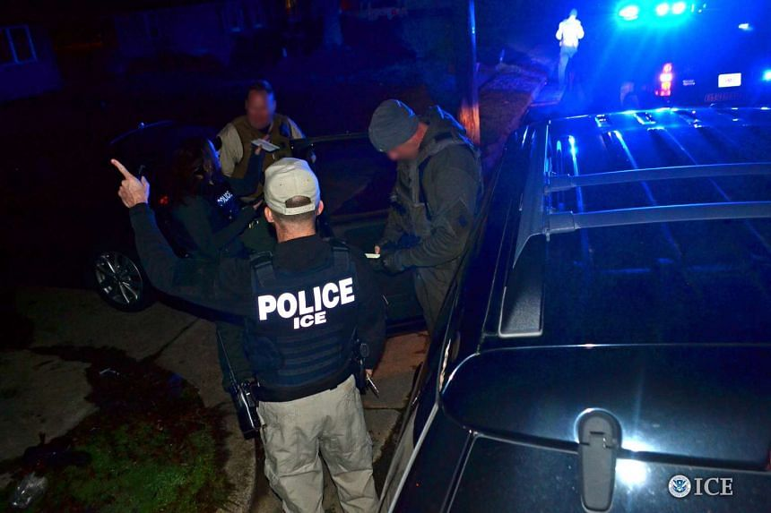US Immigration and Customs Enforcement (ICE) officers detain a suspect as they conduct a targeted enforcement operation in Los Angeles, California.