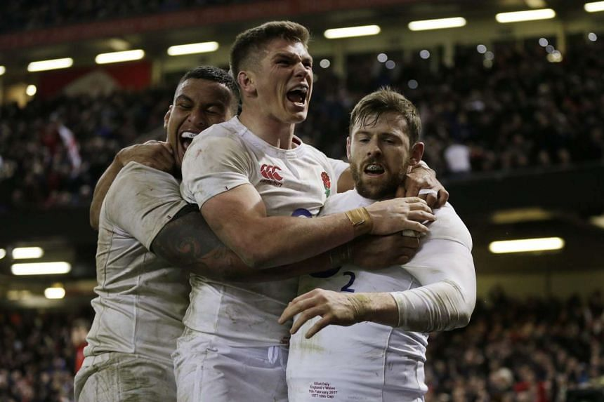 England's Elliot Daly celebrates scoring a try with teammates.