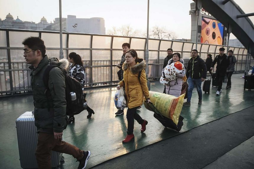 Travellers carry their luggage on a bridge next to the Beijing railway station in Beijing, China on Feb 3, 2017.