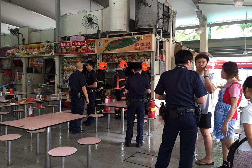 Police officers and firefighters investigate a nasi lemak stall at Block 90 Whampoa Makan Place after it caught fire on Sunday (Feb 12).