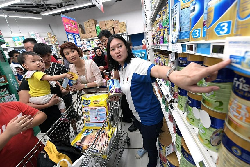 South West District Mayor Low Yen Ling (in pink) and FairPrice volunteer Grace Lin helping Madam Mok Lu Yee (holding her child), 43, shop for milk powder at a FairPrice outlet yesterday.