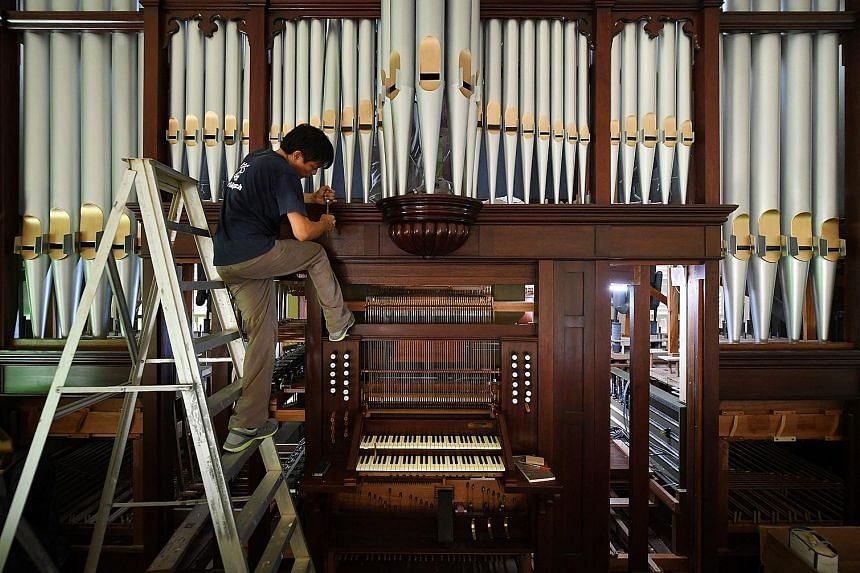 """Organ builder Cealwyn Tagle (above) adjusted various parts of each pipe by carefully tapping the metal parts or shaving off tiny bits of wood until it """"spoke"""" with the correct sound. The 105-year-old pipe organ had to be taken apart and reassembled d"""