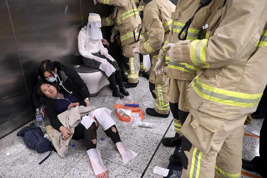 Passengers receiving medical assistance from Hong Kong rescue personnel after a fire broke out inside a Mass Transit Railway train on Friday at Tsim Sha Tsui station.